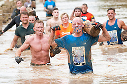 © Licensed to London News Pictures. 13/07/2014. Perton, Staffordshire, UK. Competitors take part in the Tough Fun Nettle Warrior contest. The main Tough Fun Nettle Warrior contests are 17km & 21km summer versions of the legendary 15km Tough Guy winter 'marathon assault course' event with chest high nettles and high temperatures thrown in. They include an extra lap of the notorious area called The Killing Fields. Photo credit : Graham M. Lawrence/LNP