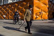 A classically-dressed English gentleman walks past the temporary renovation hoarding of luxury brand Louis Vuitton in New Bond Street, on 27th February 2019, in London, England.