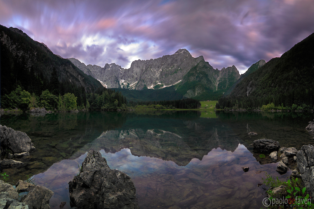 "This is the upper lake (of two) of Fusine Valromana nearby Tarvisio in Friuli, Italy, almost certainly one of the best spot of the Giulian Alps, right at the border with Austria and Slovenia. Mount Mangart is the name of the range in the background..I love the contrast here between the stormy sky and the perfectly still waters of the lake. Taken about 45 minutes after sunset, this is stitched from six vertical takes of 30"" @f11 each."