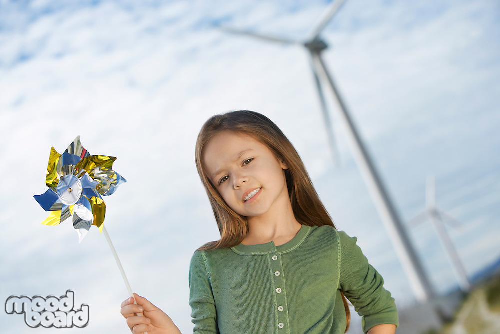 Girl (5-6) holding toy windmill at wind farm, portrait