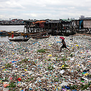 A man wades through the piles of rubbish in the Baseco area of Tondo on October 9, 2008 in Manila, the Philippines. Photo Tim Clayton