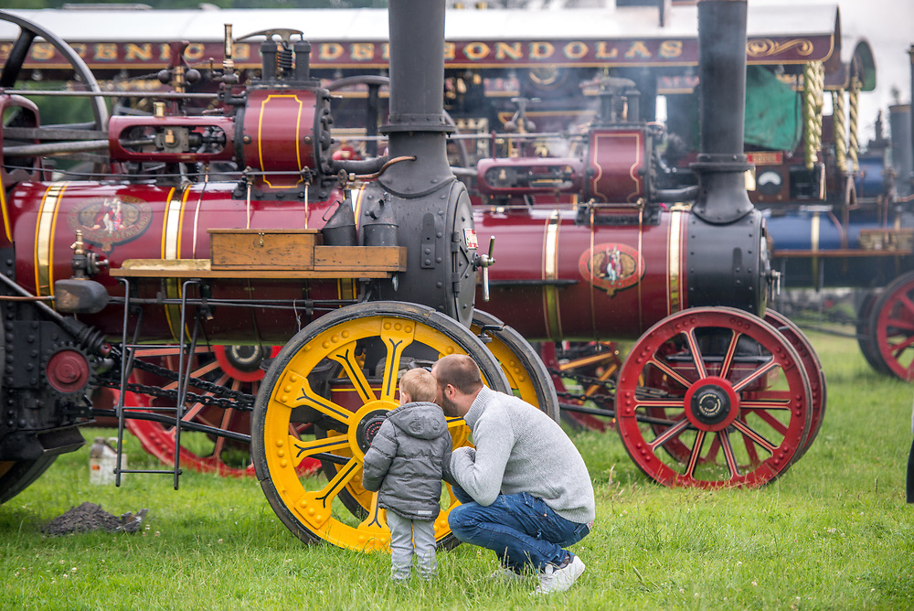 Father shows his curious son a steam engine tractor, Masham, North Yorkshire, UK