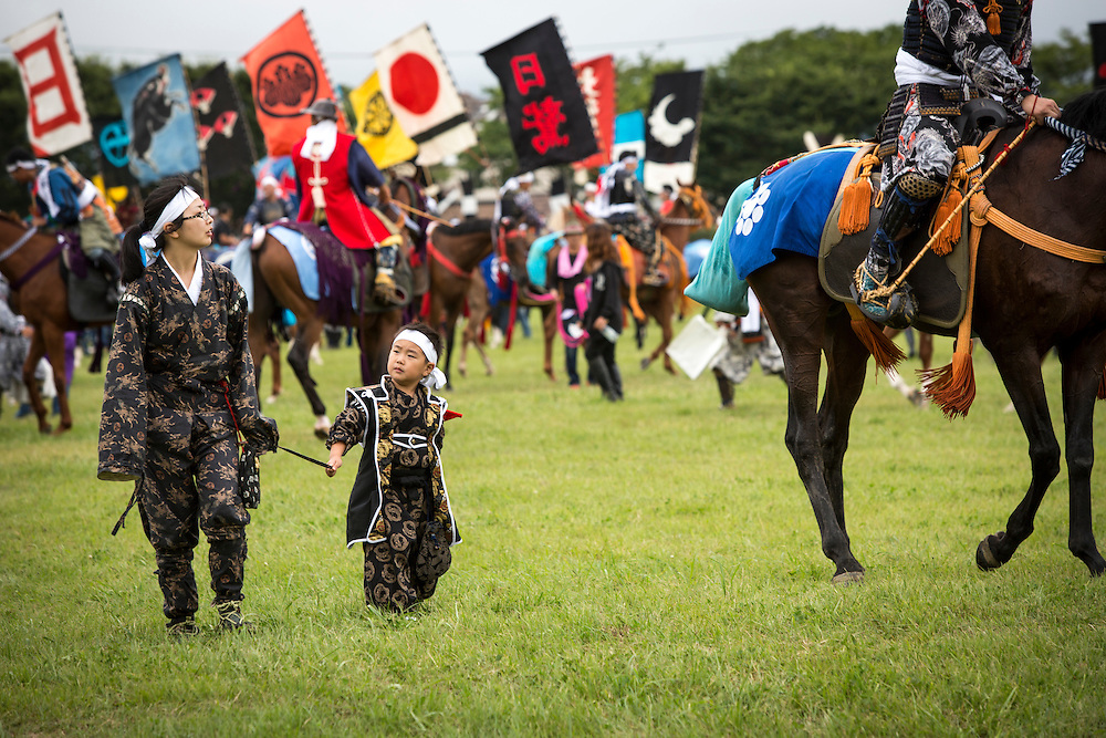 """MINAMISOMA, JAPAN - JULY 24 :  An family of samurai horseman is seen in the field before the Shinki-soudatsusen (sacred flag competition) starts, during the Soma Nomaoi festival at Hibarigahara field on Sunday, July 24, 2016 in Minamisoma, Fukushima Prefecture, Japan. """"Soma-Nomaoi"""" is a three day traditional festival that recreates a samurai battle scene from more than 1,000 years ago. The festival has gathered more than thousands visitors as Fukushima still continues to recovery from the 2011 nuclear disaster, the samurai warriors battles for recovery of the area. (Photo: Richard Atrero de Guzman/NURPhoto)"""