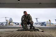 A U.S. Air Force aerial port squadron transport specialist prepares a cargo net for a waiting aircraft...Air Force aircraft transport most of the supplies and military equipment to the combat zone. Specialists must weigh, sort and load all of the gear before it heads to its location abroad.