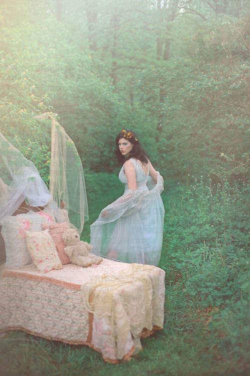 A pretty girl with dark hair in a fancy pale blue nightgown turns away from a little child's bed sitting in the woods