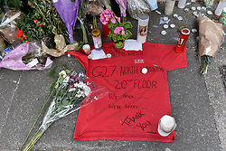 © Licensed to London News Pictures. 23/06/2017. London, UK. A nearby memorial dedicated to the victims of the fire includes signed T shirts worn by firefighters who attended the blaze.  Nine days on, police have reported that the Grenfell Tower fire in west London started in a fridge-freezer, and outside cladding and insulation failed safety tests. Photo credit : Stephen Chung/LNP