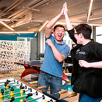 Workers at Enova, a Chicago based FinTech company high five each other during a friendly game of Foosball during a break from work.