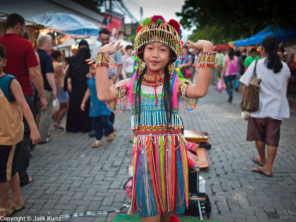 "26 JUNE 2011 - CHIANG MAI, THAILAND: A Lisu girl performs for tourists in the ""Walking Street"" market in Chiang Mai, Thailand. The Walking Street market is a weekly, Sunday night, market along Ratchadamnoen Street in Chiang Mai. The Lisu are a Tibeto-Burman highland tribe, originally from southwest China. They can be found in China, India, Myanmar. A few drifted into North Thailand from Burma Kengtung.  PHOTO BY JACK KURTZ"