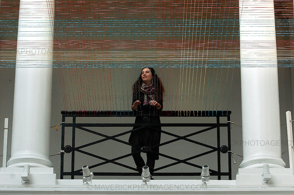 Edinburgh College of Art Master of Fine Art student Daniela Justiniano has created the latest in a series of rubber bands installations, a vast elastic tartan, in the College Sculpture Court...The work has been made with 25,350 colored elastic bands. The 27 year old artist from Santiago, Chile, spent three weeks assembling the work and installing the elastic chains across the balcony of the Sculpture Court.