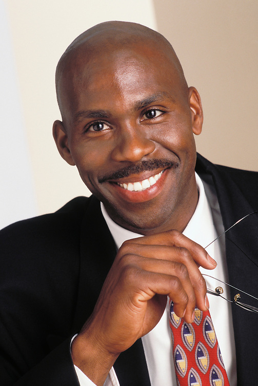 Portrait of an African American business man holding his glasses and smiling.<br />