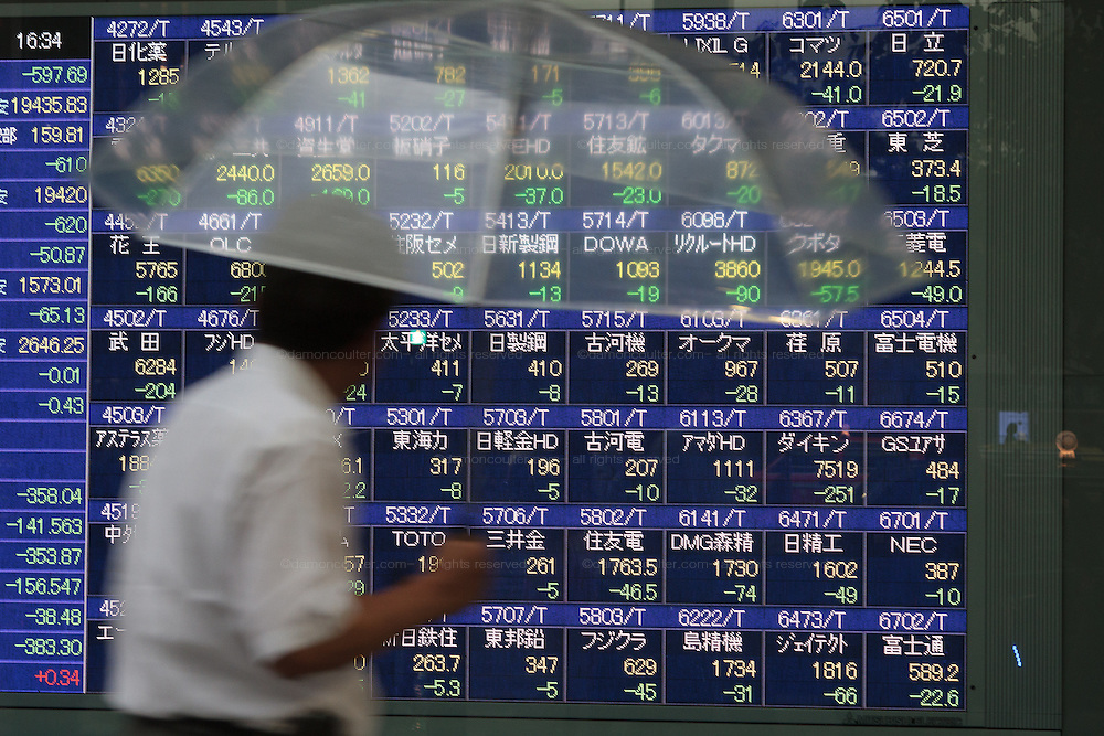 A Japanerse office worker or salaryman, holding an umbrella, looks at the stock prrices in the window of a bank near Tokyo Station. Tokyo, Japan. Friday August 21st 2015