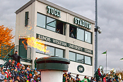 18 October 2014:  Tucci Staium and the crowd act as a backdrop to the victory torch during an NCAA division 3 football game between the Augustana Vikings and the Illinois Wesleyan Titans in Tucci Stadium on Wilder Field, Bloomington IL<br /> <br /> This image has had HDR (High Dynamic Range) processing applied