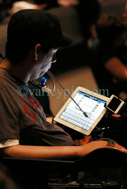 17 May 2013. New Orleans, Louisiana,  USA..A man in a  wheelchair checks his iPad at the Morial Convention Center as he awaits an address from His Holiness the 14th Dalai Lama in New Orleans for the 'Resiliance - Strength through Compassion and Connection' conference. .Photo; Charlie Varley.