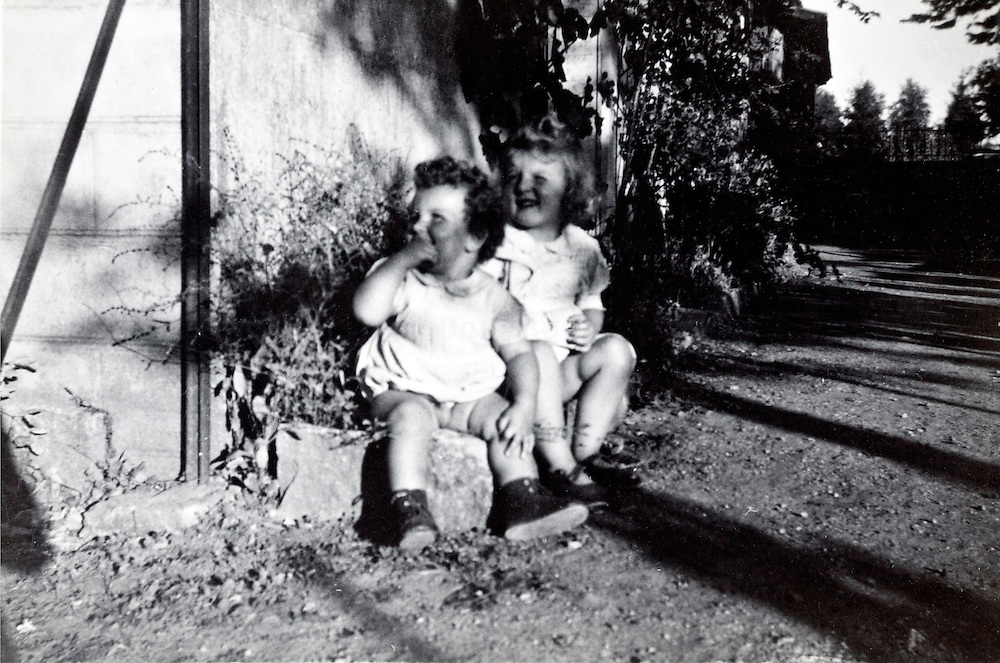 toddler sisters sitting in the sun France vintage