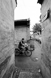 Man cycling through warren of alleys in hutong district of Beijing China