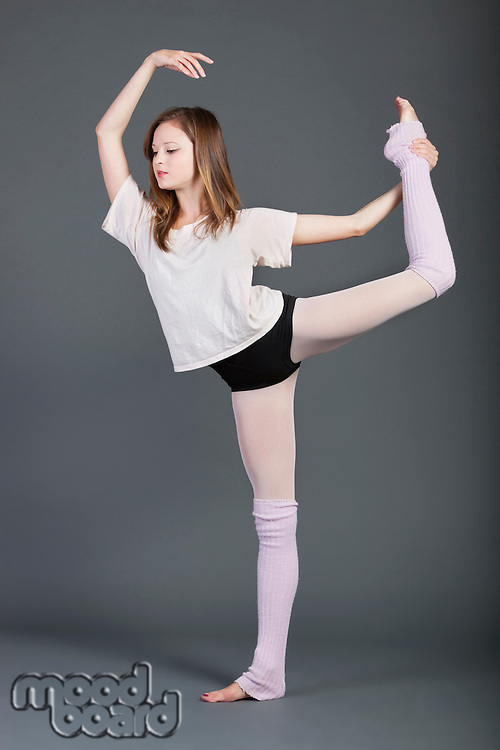 Young woman performing ballet over grey background