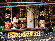 "02 AUGUST 2017 - UBUD, BALI, INDONESIA: A Hindu priest hits a prayer gong during the ""Merchants' Day"" ceremony at the Pura (Temple) Melanting Pasar Ubud, the small Hindu temple in the Ubud market. It's a day that merchants throughout Ubud come to the temple to make offerings and pray for prosperity.    PHOTO BY JACK KURTZ"