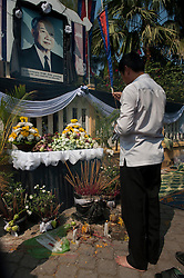 © Licensed to London News Pictures. 01/02/2013. Location, Cambodia. Mourner prays infront of a portrait of  the Late former King Norodom Sihanouk. Thousands of mourners lined the streets of Phnom Penh as part of the late kings royal funeral procession ahead of his Feb. 4, cremation Friday, Feb. 1, 2013, in Phnom Penh, Cambodia.  Photo credit : Charles Fox/LNP