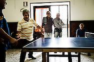 Bagnoli, Italia - 3 novembre 2011. Ex operai dell'ILVA di Bagnoli, membri del circolo ILVA, giocano a ping pong in una delle sale del circolo. La riqualificazione dell'area, dopo 20 anni, è ancora da compiersi. Con l'arrivo di due tappe della celebre competizione velica dell'America's Cup nello specchio d'acqua compreso tra Nisida e Pozzuoli, si spera in un'accelerazione del processo di bonifica e riqualificazione del territorio. si  Ph. Roberto Salomone Ag. Controluce.ITALY - Former ILVA workers play ping pomg in the ILVA recreational center, which they are mebers of. The area should be requalified after more than 20 years of abandon. Two rounds of the America's Cup sailing competition will be hosted in Bagnoli in the next months; this should give a boost to the requalification of the entire area.