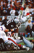 An unidentified Denver Broncos defender goes upside down as he tried to dive and stop Los Angeles Raiders running back Napoleon McCallum (41) from diving over the goal line and scoring a touchdown during the 1994 NFL AFC Wild Card playoff football game against the Denver Broncos on Jan. 9, 1994 in Los Angeles. The Raiders won the game 42-24. (©Paul Anthony Spinelli)