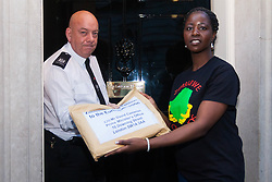A delegation of Zimbabweans from the weekly Zimbabwe Vigil protest that has been held at Zimbabwe House in London for over 10 years, delivered a petition to Downing Street objecting to the lifting of EU sanctions against the aging Mugabe's regime despite the fact that there have been no political reforms in the country whose large population in the diaspora are denied their right to vote, and where rigging and intimidation are the order of the day in Presidential and Parliamentary elections. PICTURED: A woman from Zimbabwe Vigil passes their petition to a Downing Street representative.