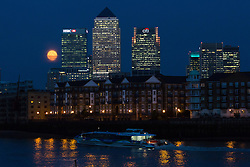 © Licensed to London News Pictures. 09/09/2014. London, UK. A supermoon is seen rising behind the Canary Wharf financial district in London as a commuter boat passes on the River Thames on 9th September 2014.  Photo credit : Vickie Flores/LNP.