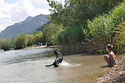 Schliersee, Upper Bavaria, Germany. A boy and his pet dog in the water
