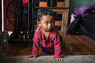Sujal Tamang (2) crawls around on the floor in his aunt's apartment on the 5th floor in Jorpati, Kathmandu, Nepal on 2 July 2015. Sujal was buried under the rubble of his collapsed house for 36 hours before rescuers found him injured with a broken leg next to his mother who was killed on the spot. Photo by Suzanne Lee for SOS Children's Villages