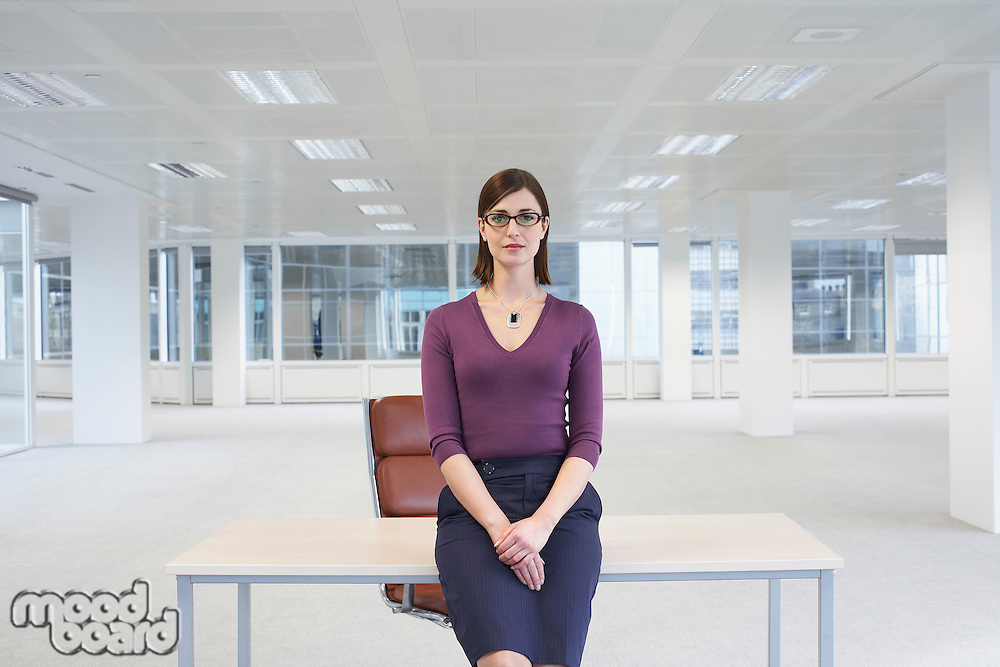 Female office worker sitting on edge of table in empty office space