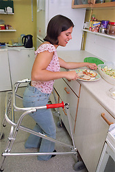Teenage girl with physical disability preparing sandwich in kitchen of residential respite care home,