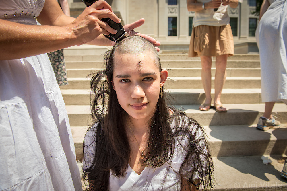 """On the steps of the West Virginia State Capitol, Paula Swearengin shaves the head of Tori Wong of Virginia. The shaving of their heads was symbolic of the mountains that have been stripped of all of the living things on them. It was also symbolic of the many people who are sick or dying as the result of Mountaintop Removal. Mountaintop Removal is a method of surface mining that literally removes the tops of mountains to get to the coal seams beneath. It is the most profitable mining technique available because it is performed quickly, cheaply and comes with hefty economic benefits for the mining companies, most of which are located out of state. It is the most profitable mining technique available because it is performed quickly, cheaply and comes with hefty economic benefits for the mining companies, most of which are located out of state. Many argue that they have brought wage-paying jobs and modern amenities to Appalachia, but others say they have only demolished an estimated 1.4 million acres of forested hills, buried an estimated 2,000 miles of streams, poisoned drinking water, and wiped whole towns from the map. """"Watch out, King Coal,"""" Swearengin said, """"because here come the Queens of Appalachia."""" © Ami Vitale"""