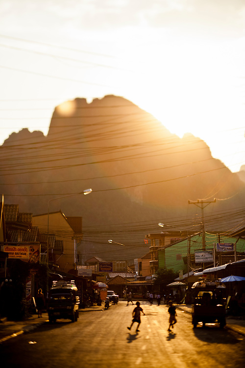 Children play in the streets at dusk in Vang Vien, Laos.