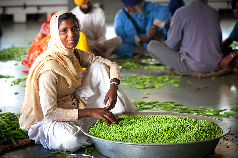 A volunteer peels peas at a Sikh kitchen in Punjab,India.Vo The sikh kitchen provides ten of thousands of free meals on a daily basis. The main work force at the Sikh kitchen is made of Sikh volunteers.