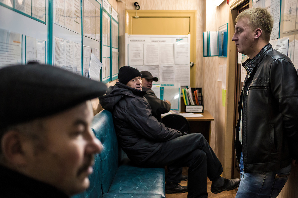 Men sit in an employment office on Wednesday, October 23, 2013 in Baikalsk, Russia.