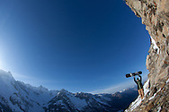 A snowboarder celebrates the view from a rocky vantage point in the swiss alps, March 2011(Photo ©Lee Irvine www.slikimages.com)