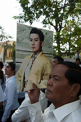 © Licensed to London News Pictures. 01/02/2013. Location, Cambodia. Mourner holds a picture depicting the depicting the Late former King Norodom Sihanouk as a young man. Thousands of mourners lined the streets of Phnom Penh as part of the late kings royal funeral procession ahead of his Feb. 4, cremation Friday, Feb. 1, 2013, in Phnom Penh, Cambodia.  Photo credit : Charles Fox/LNP