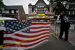 An American Flag is draped over police tape as protestors and fans face off on opposing sides of the street ahead of a tour stop by Tomi Lahren, conservative political commentator and Fox News contributor, at the Keswick Theatre in Glenside, PA on May 17, 2018. Across the street from the Philadelphia suburban theatre a group of demonstrators stage a protest to oppose Lahren's political views.
