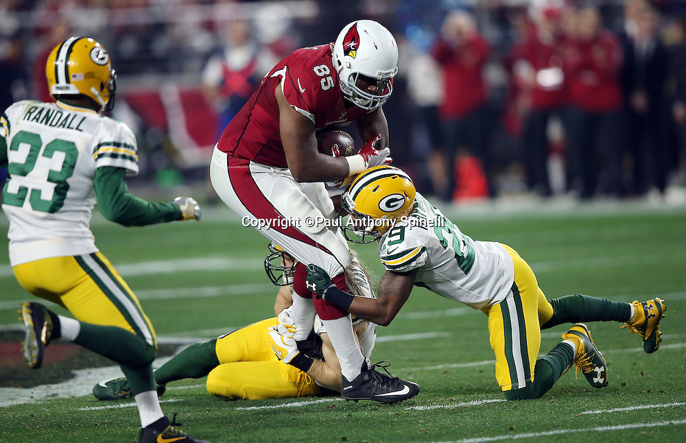 Arizona Cardinals tight end Darren Fells (85) gets gang tackled by Green Bay Packers inside linebacker Clay Matthews (52) and Green Bay Packers cornerback Casey Hayward (29) on a play that leads to a first down due to an unnecessary roughness penalty on Green Bay Packers nose tackle B.J. Raji (90) during the NFL NFC Divisional round playoff football game against the Green Bay Packers on Saturday, Jan. 16, 2016 in Glendale, Ariz. The Cardinals won the game in overtime 26-20. (©Paul Anthony Spinelli)