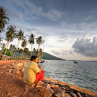 Older woman watches sunset from small fishing village near Sihanoukville, Cambodia