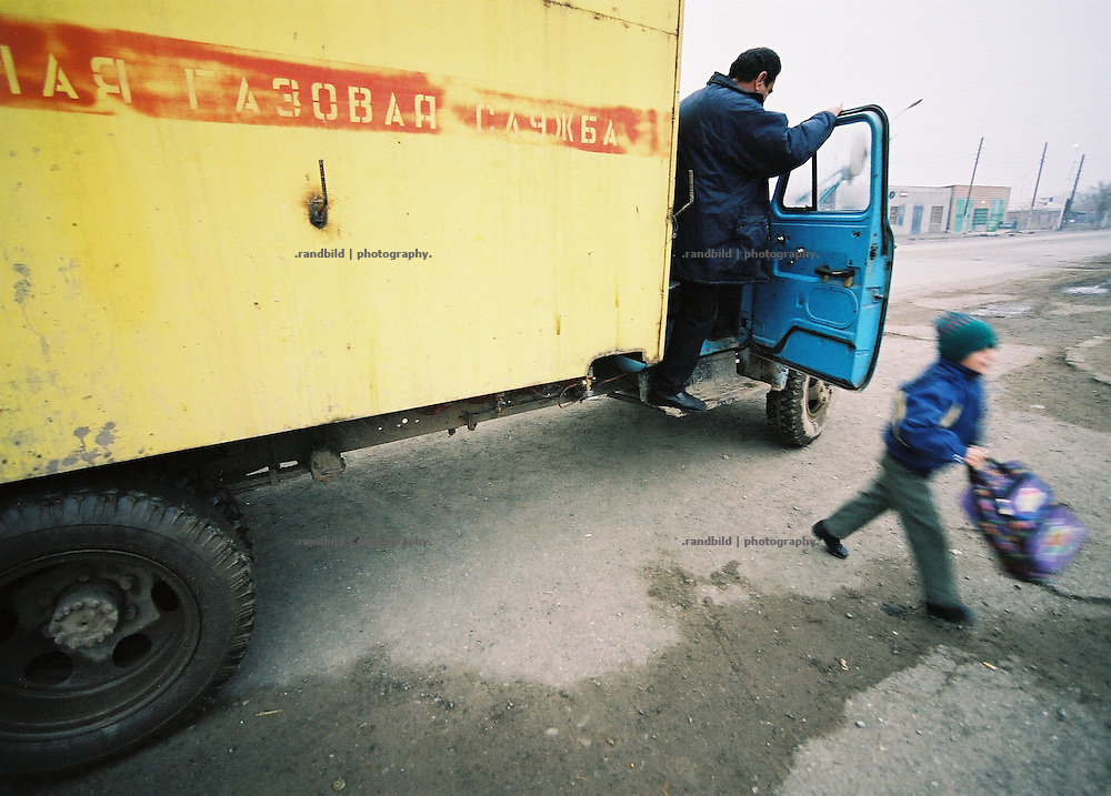 A boy jumps out of a truck brining him to his school in westarmenian village Hoktember.
