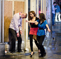 © Licensed to London News Pictures. FILE PICTURE DATED  01/01/2012. New Years Day revellers in Manchester. A man struggles to keep himself standing up in a doorway as two women walk by. Please see special instructions for usage rates. Photo credit should read Joel Goodman/LNP