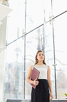 Confident businesswoman holding folder at office lobby