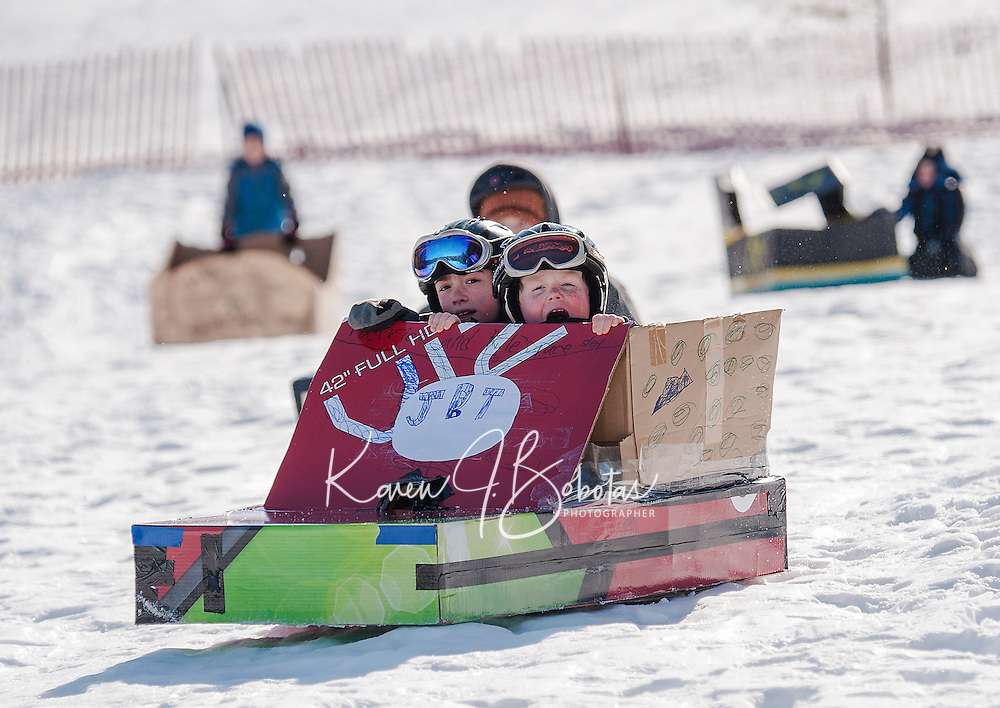 "Patrick and Kyle Gandini hold on tight as their ""78er"" gains speed during the annual Cardboard Sled Derby with Gilford Parks and Recreation at the Gilford Outing Club Wednesday morning.  The Gandini brothers took 2nd in the Best Use of Cardboard and 1st in the Fastest Sled (-10) Division.    (Karen Bobotas/for the Laconia Daily Sun)"