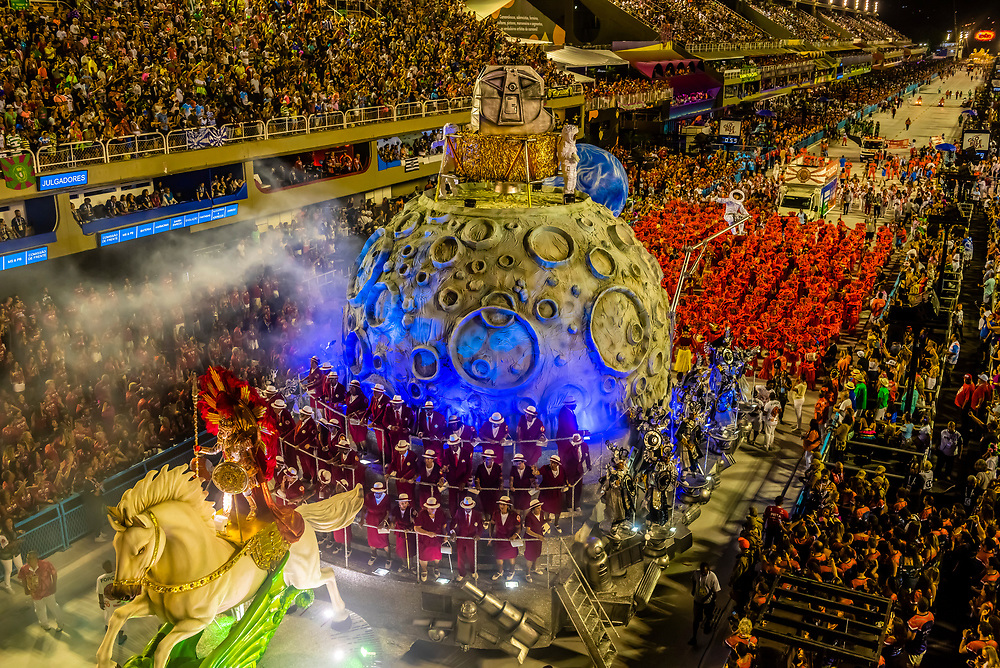 """Floats in in the Carnaval parade of Estacio de Sa samba school in the Sambadrome, Rio de Janeiro, Brazil.           <br /> <br /> The theme  of their parade is """"Stones"""" which includes a 2001:A Space Odyssey type scene with cavemen watching a rock open into a spacecraft with astronauts coming out."""