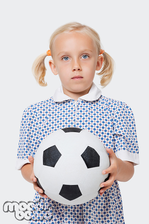 Portrait of a young girl holding soccer ball over white background