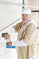 Portrait of a mature man holding construction equipment