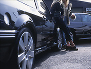 Girl racers with their cars, UK, 2000's.