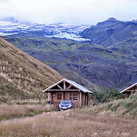 Small house, car & mountains with Eyjafjallajokull glacier, dusk.