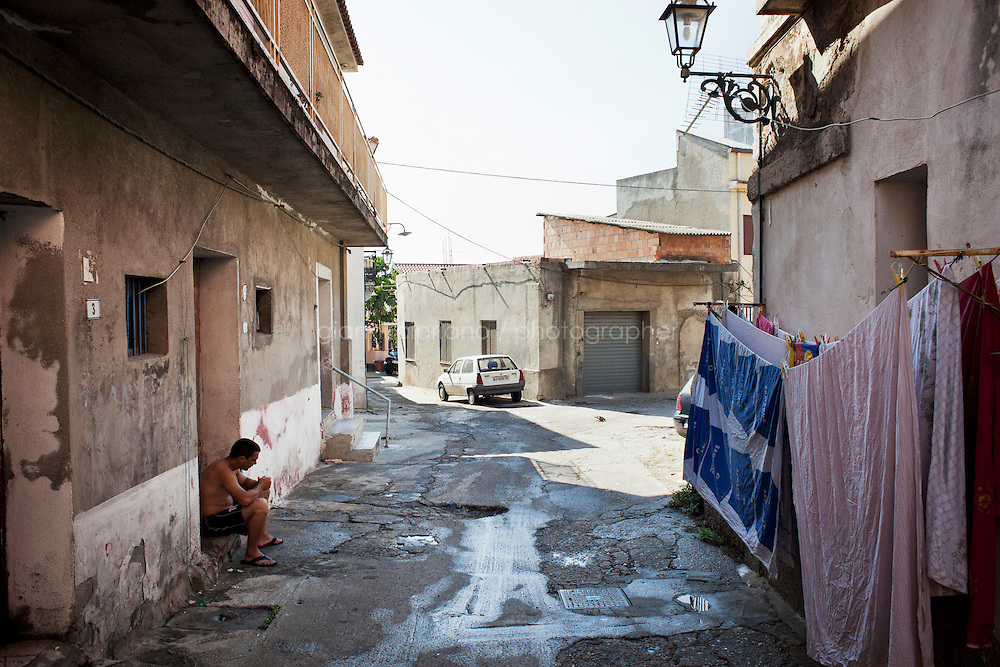 Gioia Tauro, Italy - 31 August, 2012: A young man sits on the side of the road in Gioia Tauro, Italy, a mafia stronghold on August 31, 2012. The current mayor of Gioia Tauro, Renato Bellofiore, was elected in 2010 after the former mayor and deputy mayor, Giorgio Dal Torrione and Rosario Schiavone, were arrested on Mafia charges in 2008. Both had been forced to step down when the city council was dissolved on suspicion of Mafia infiltration. Gioia Tauro is a city of 19,000 people built on an ancient Greek necrapolis and that today has the largest seaport in Italy and the sevent largest container port in Europe with its extension of 4,646 meters. Because the port is not connected to adeguate roads or rails, the ships mostly transfer containers to smaller vessels and little economic activity stays local. To authorities, the port is best known as the first point of entry for most of the cocaine that enters Europe from South America. In a routine rais earlier this month, authorities seized 176 kilos of pure cocaine with an estimated street value of 38 million euros.<br /> <br /> Calabria is one of the poorest Italian regions which suffers from lack of basic services (hospitals without proper equipment, irregular electricity and water), the product of disparate political interests vying for power. The region is dominated by the 'Ndrangheta (pronounced en-Drang-get-A), which authorities say is the most powerful in Italy because it is the welthiest and best organized.<br /> <br /> The region today has nearly 20 percent unemployment, 40 percent youth unemployment and among the lowest female unemployment and broadband Internet levels in Italy. Business suffer since poor infrastructure drives up transport costs.<br /> <br /> Last summer the European Union's anti-fraud office demanded that Italy redirect 380 million euros in structural funding away from the A3 Salerno - Reggio Calabria highway after finding widespread evidence of corruption in the bidding processes.