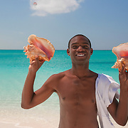 Friendly man selling conch shells on the beach at Grace Bay in Providenciales, Turks and Caicos